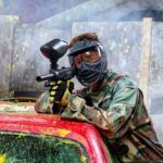 Jonge man richt paintball geweer bij paintball Hillegom